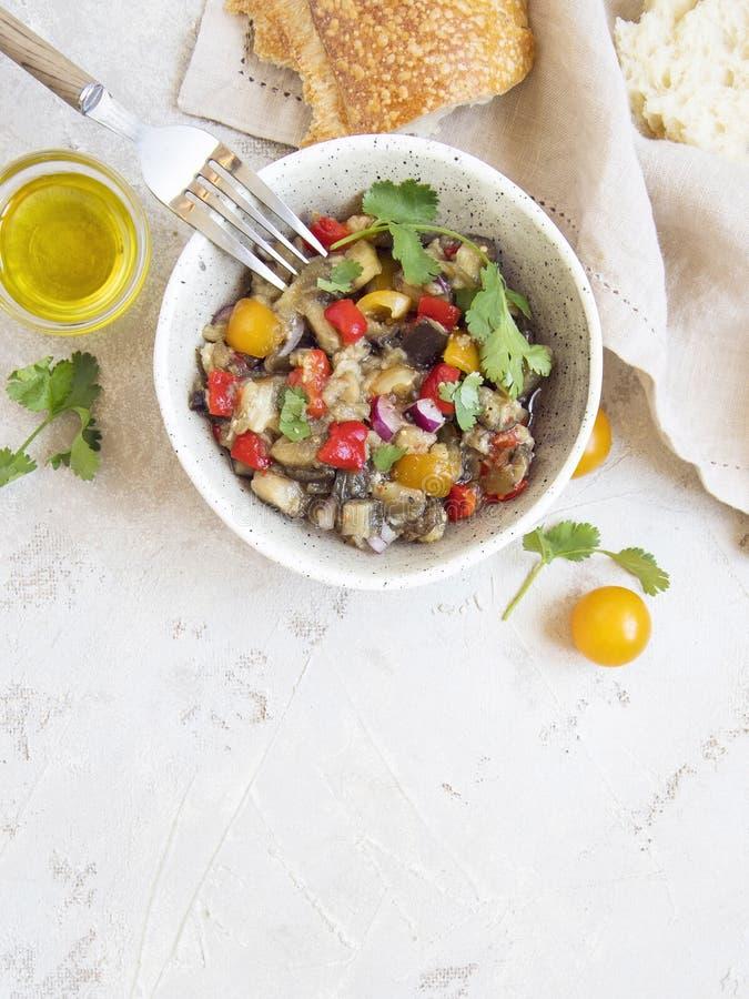 Salade met gebakken aubergines, paprika, tomaten, zoete rode ui, olie en koriander stock afbeeldingen