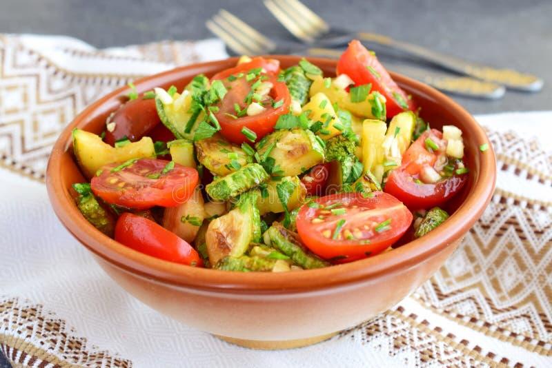 Salade met gebraden courgette en verse kersentomaten, basilicum, knoflook en olijfolie royalty-vrije stock afbeelding