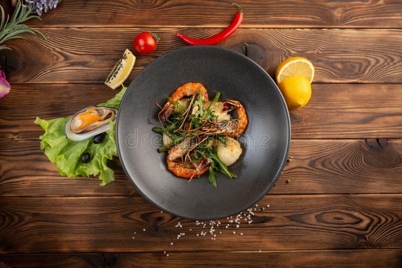 salade met geroosterde garnalen en knapperige groenten in een plaat op een houten achtergrond stock afbeelding