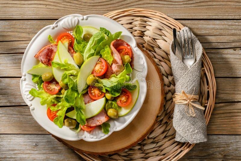 Salade met geroosterde ham, tomaten, appelen en groene olijven royalty-vrije stock foto