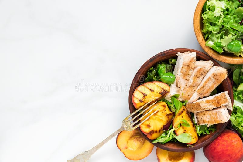 Salade met geroosterde kip en perzik in een kom met vork Gezond voedsel Hoogste mening stock afbeeldingen