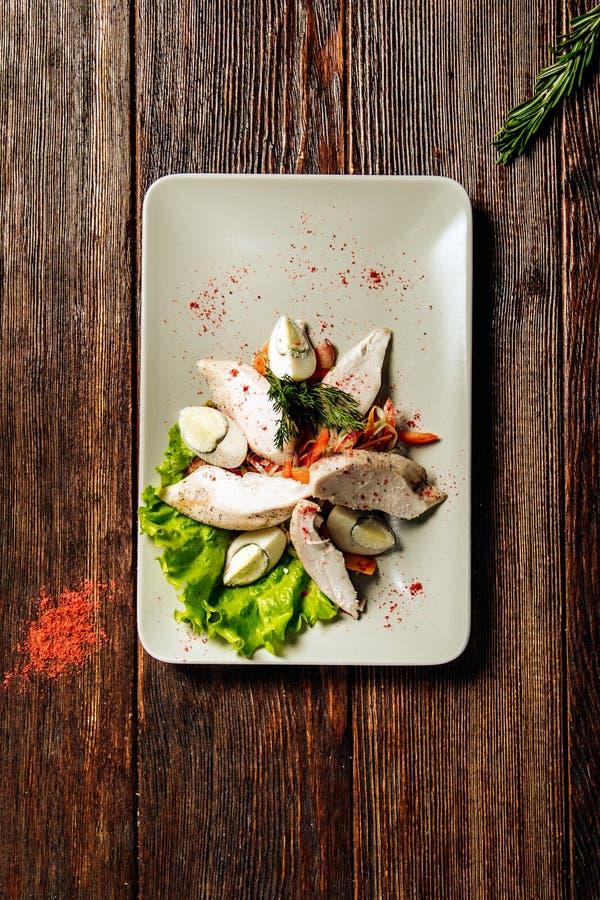 Salade met gevulde kippenfilet en eieren op witte plaat op houten achtergrond royalty-vrije stock afbeeldingen
