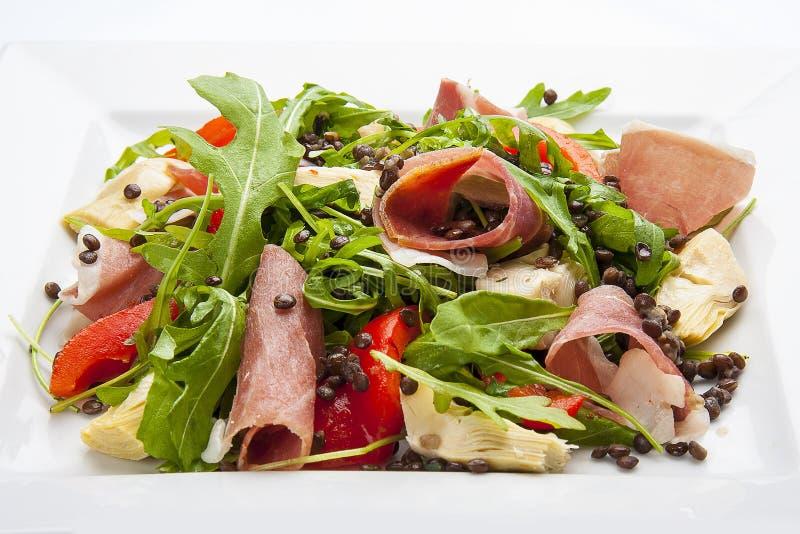Salade met prosciutto en artisjokken op een witte plaat stock fotografie
