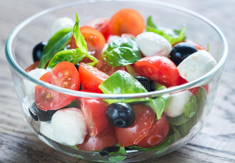 Salade met tomaten, olijven, mozarella en basilicum royalty-vrije stock afbeeldingen