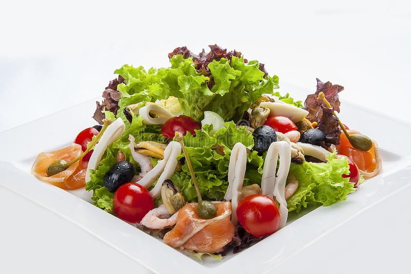 Salade met zalm en zeevruchten op een witte plaat stock foto's