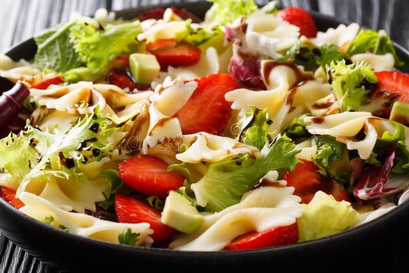 Salade organique de farfalle de pâtes avec l'avocat, fraises, laitue, préparée avec le plan rapproché balsamique de sauce horizon photos libres de droits