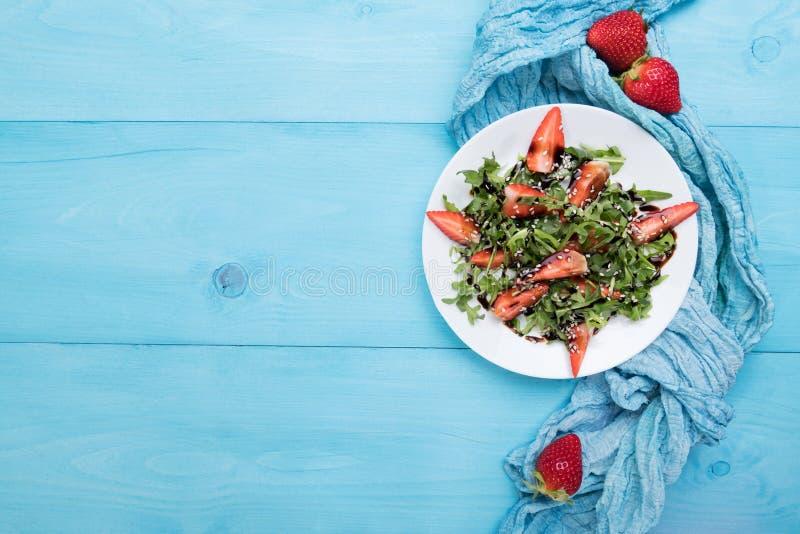 Salade organique saine de régime avec l'arugula, les fraises et le sésame avec le lustre balsamique dans le plateon blanc un en b image libre de droits