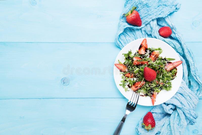 Salade organique saine de régime avec l'arugula, les fraises et le sésame avec le lustre balsamique dans le plateon blanc un en b photographie stock