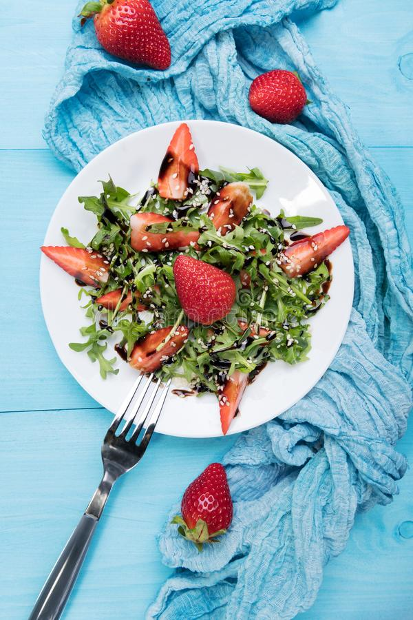 Salade organique saine de r?gime avec l'arugula, les fraises et le s?same avec le lustre balsamique dans le plateon blanc un en b photos stock