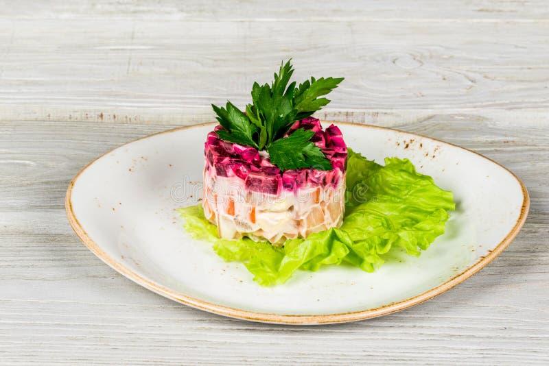 salade posée avec des harengs, des betteraves, des carottes, des oignons, des pommes de terre et des oeufs image libre de droits