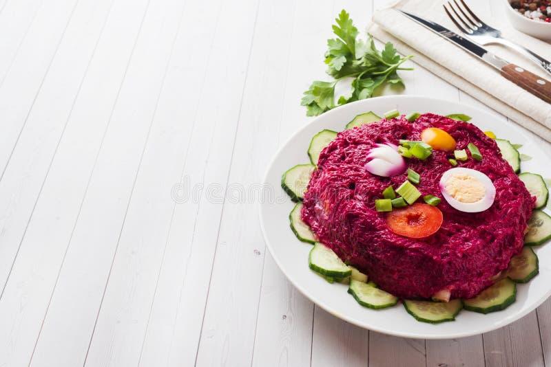 Salade posée avec des harengs et des betteraves, des carottes et des pommes de terre et des oeufs en gros plan d'un plat L'espace photographie stock