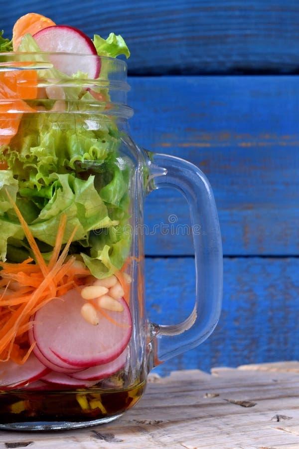 Salade pos?e dans un pot avec les mandarines, le radis, les feuilles de laitue, la carotte et le habillage image libre de droits