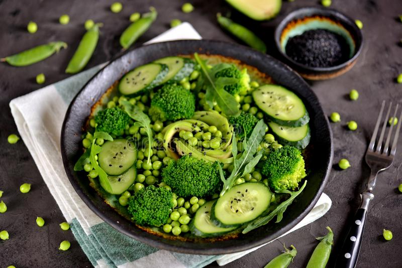 Salade saine de brocoli, de pois, de concombre et d'avocat avec l'arugula et l'huile d'olive Nourriture saine Vue supérieure photo stock