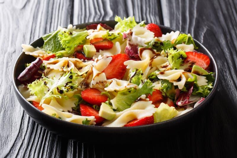 Salade saine des pâtes de farfalle avec l'avocat, les fraises, la laitue fraîche et le plan rapproché balsamique de sauce d'un pl image libre de droits