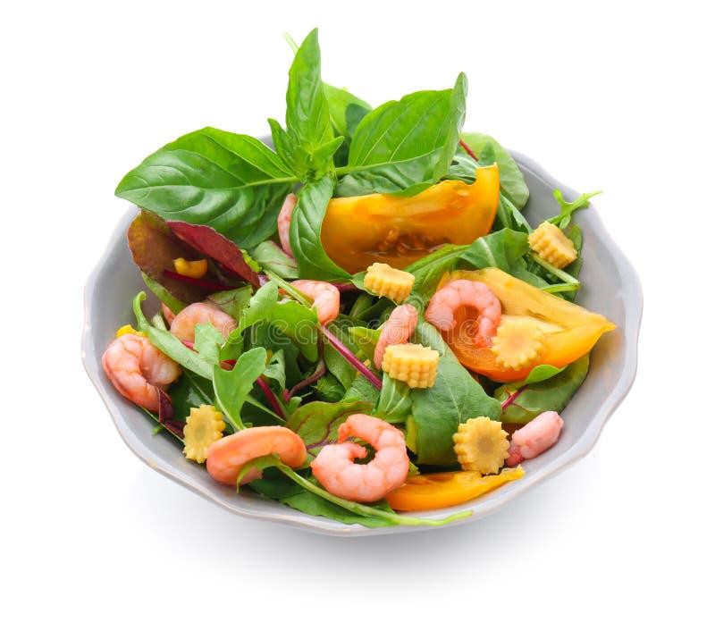 Salade savoureuse avec des crevettes et des légumes dans la cuvette sur le fond blanc image stock