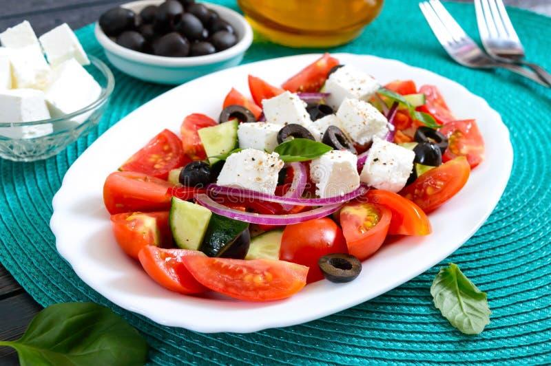 Salade savoureuse de vitamine avec les légumes frais, feta, olives noires, sauce à basilic d'un plat blanc sur un fond en bois photos libres de droits