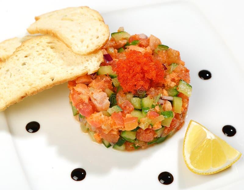 Salade teer-zalm, tonijn, komkommers, tomaten, Krimuien, salademengeling, olijfolie, kaviaar van vliegende vissen royalty-vrije stock fotografie