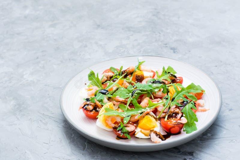 Salade tout préparée avec des tomates-cerises, des oeufs, la crevette bouillie, l'arugula, des graines de sésame et la sauce bals images stock