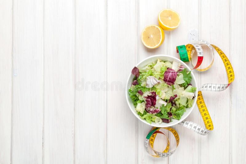 Salade, ustensiles et ruban métrique sains frais au-dessus d'en bois blanc photographie stock libre de droits
