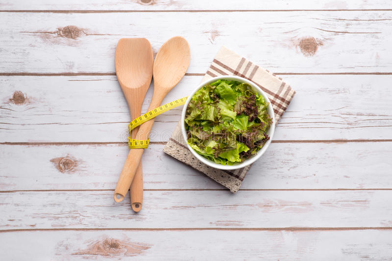 Salade, ustensiles et ruban métrique sains frais au-dessus d'en bois blanc image stock