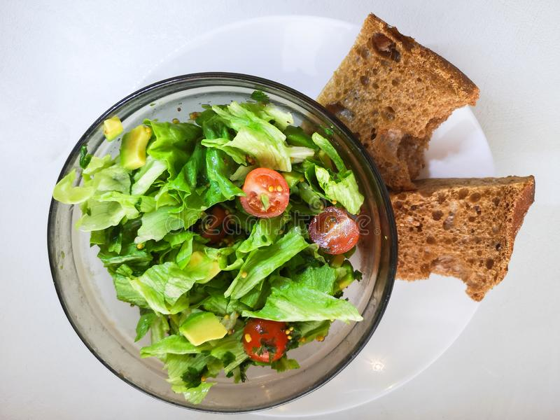 Salade végétale avec Breadon un plat blanc, avec du pain sur un conseil profond nourriture saine, petit déjeuner vert images libres de droits