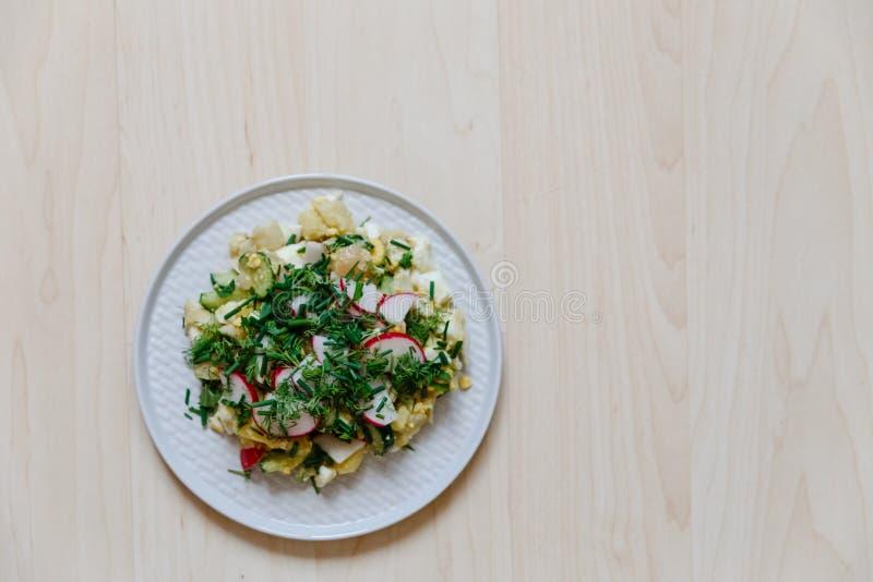 Salade végétale avec le radis, les concombres frais, les pommes de terre et les oignons verts sur une vue supérieure de plat blan images stock