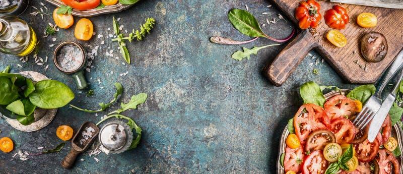 Salade végétarienne saine faisant la préparation avec des tomates sur le fond rustique, vue supérieure photo stock