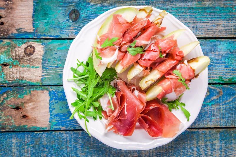 Salade van meloen met dunne plakken van prosciutto, arugulabladeren en balsemieke saus hoogste mening stock foto