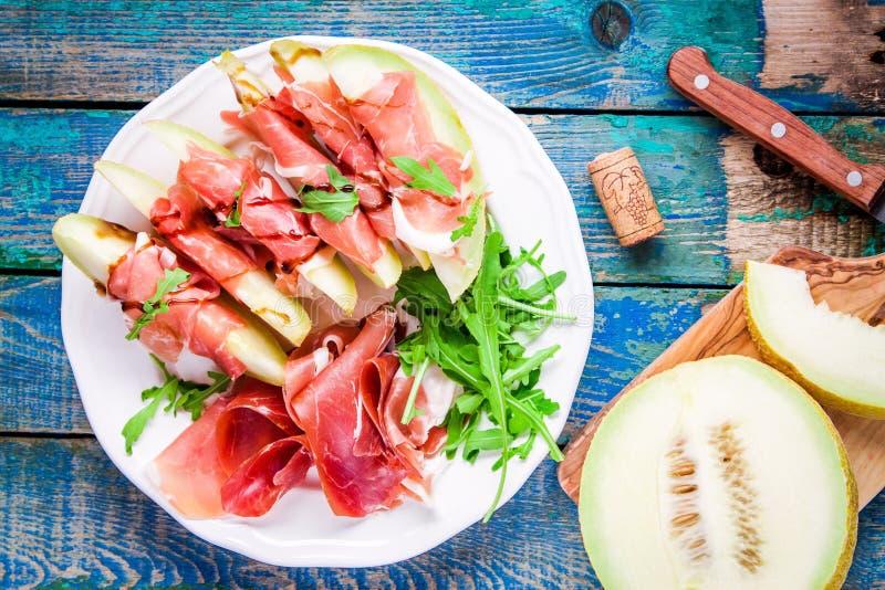 Salade van meloen met dunne plakken van prosciutto, arugulabladeren en balsemieke saus hoogste mening stock fotografie
