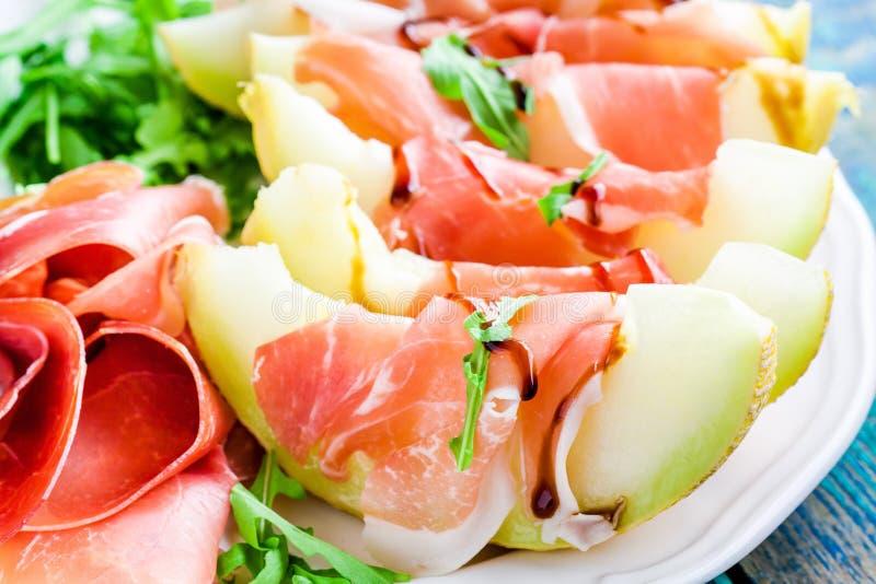 Salade van meloen met dunne plakken van prosciutto, arugulabladeren en balsemieke sausclose-up stock afbeeldingen
