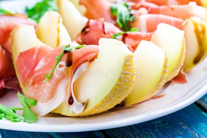 Salade van meloen met dunne plakken van prosciutto, arugulabladeren en balsemieke sausclose-up stock foto