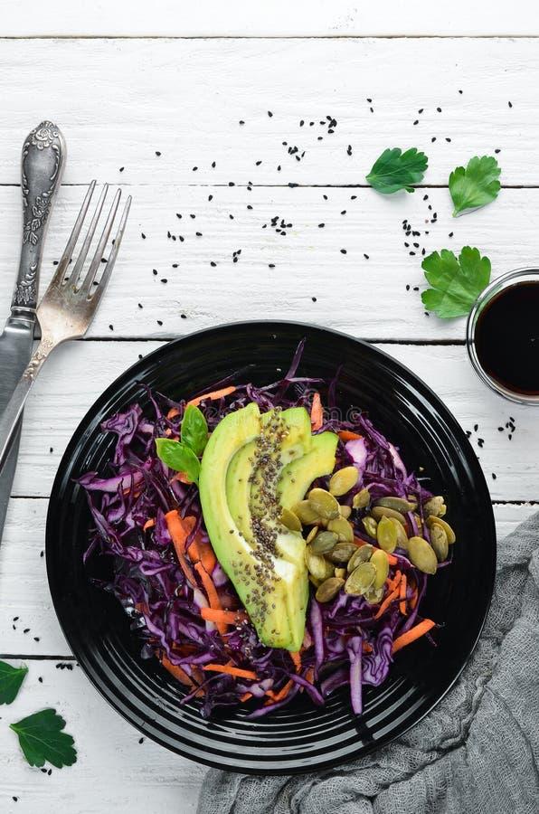 Salade van purpere kool, wortelen, avocado's en pompoenzaden stock afbeeldingen