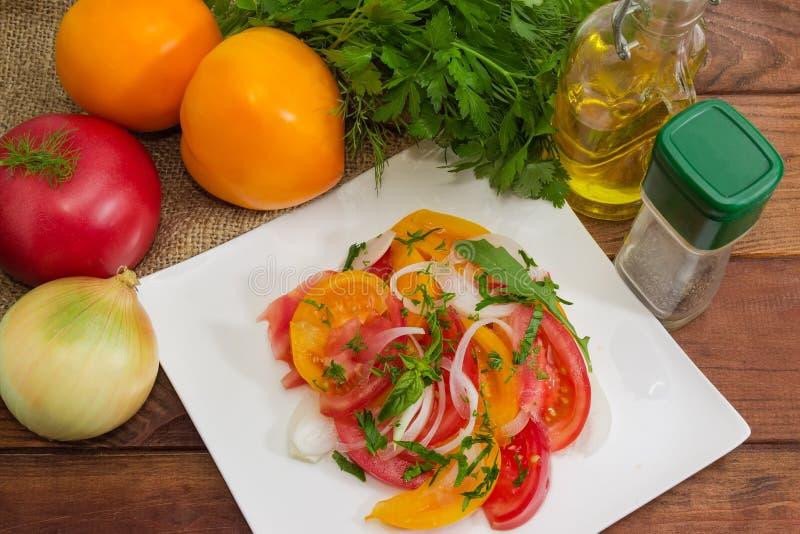 Salade van rode en gele tomaten onder ingrediënten stock foto