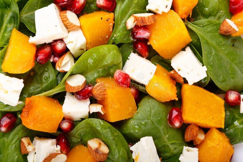 Salade van spinaziebladeren, gebakken pompoen en feta-kaas met amandelen en granaatappelzaden als achtergrond stock fotografie