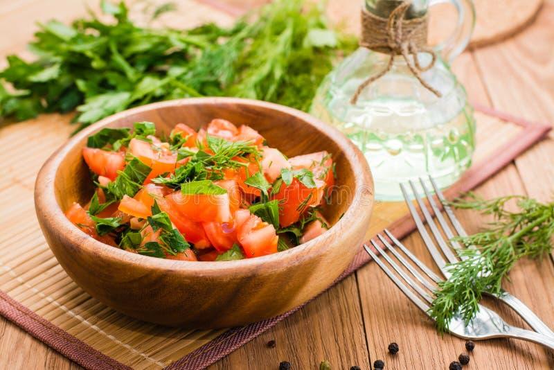 Salade van tomaten en verse kruiden, plantaardige olie en vork o wordt gemaakt dat stock foto's