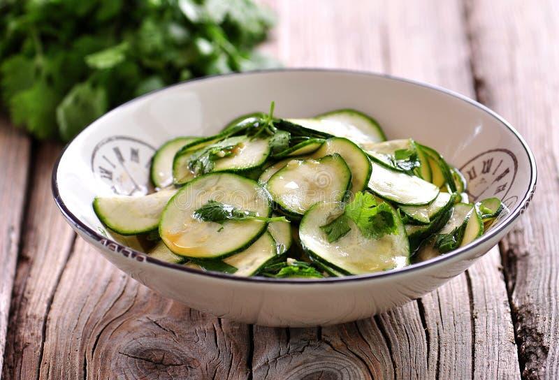 Salade van verse courgette met knoflook, koriander, olijfolie, balsemiek azijn en overzees zout stock foto's