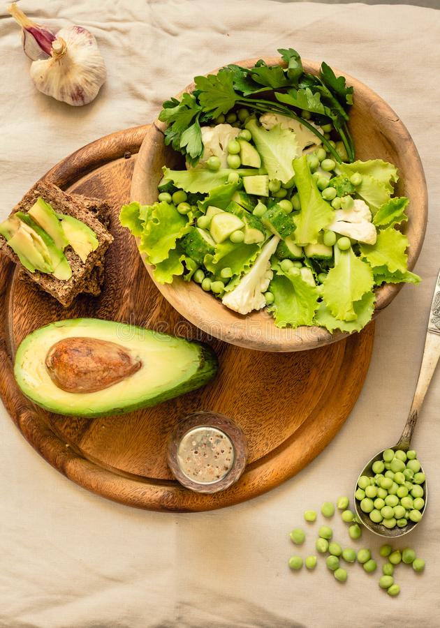 Salade verte délicieuse fraîche avec l'avocat dans une vue supérieure en bois de pain grillé libre de plat et de gluten Nourritur image stock