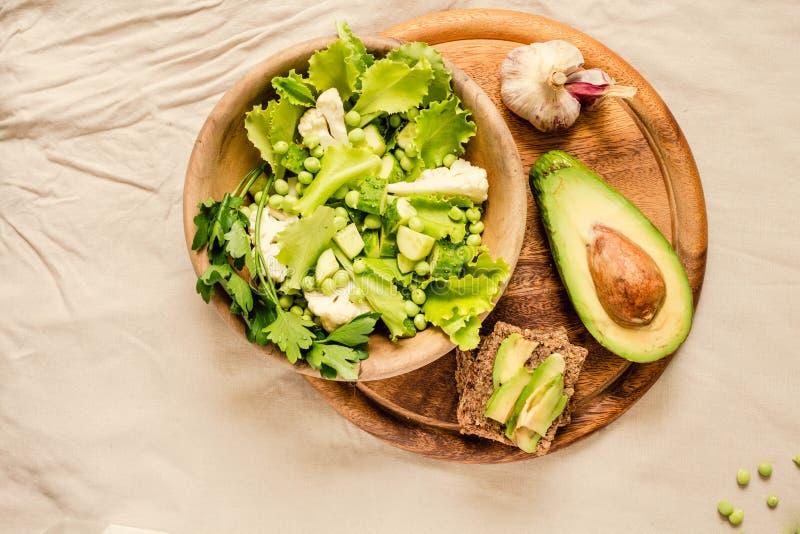 Salade verte délicieuse fraîche avec l'avocat dans une vue supérieure en bois de pain grillé libre de plat et de gluten Nourritur photos libres de droits