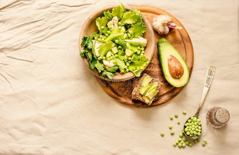 Salade verte délicieuse fraîche avec l'avocat dans une vue supérieure en bois de pain grillé libre de plat et de gluten Nourritur photographie stock