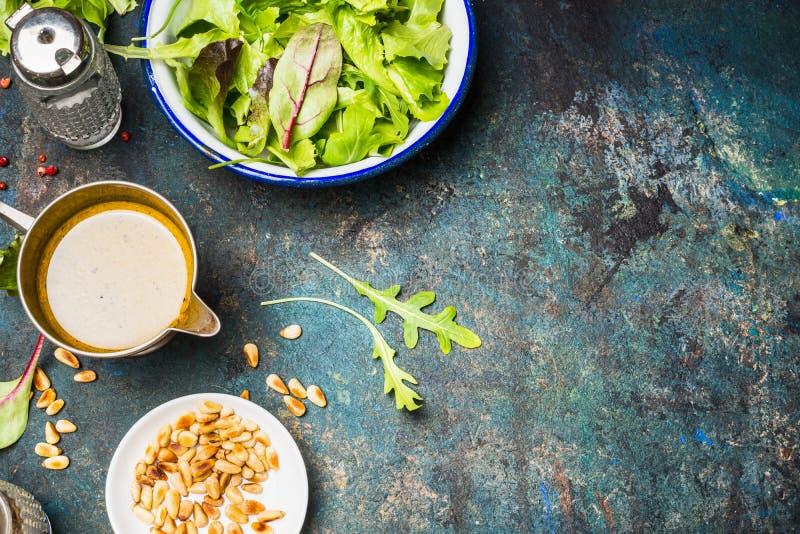 Salade verte de mélange avec le habillage d'huile et pignons sur le fond rustique photo stock