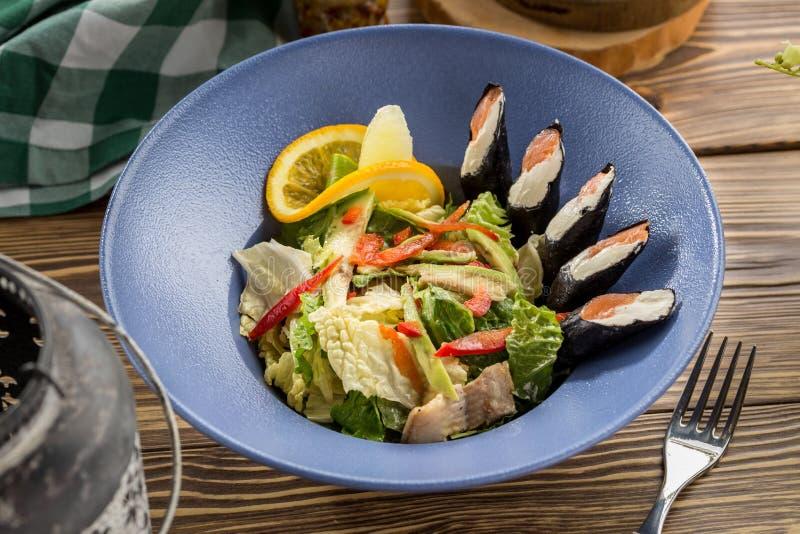Salade verte fraîche avec les sushi saumonés de fromage fondu du côté sur la table en bois photo libre de droits