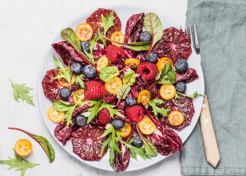 Saladeplaat met greens, sinaasappelen en bessen hoogste mening Gezond ruw voedselconcept stock afbeeldingen
