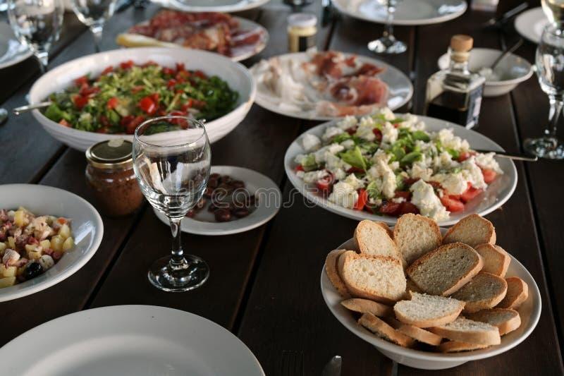 Salades méditerranéennes et antipasti sur une table posée pour un dîner rustique en plein air le soir photo stock