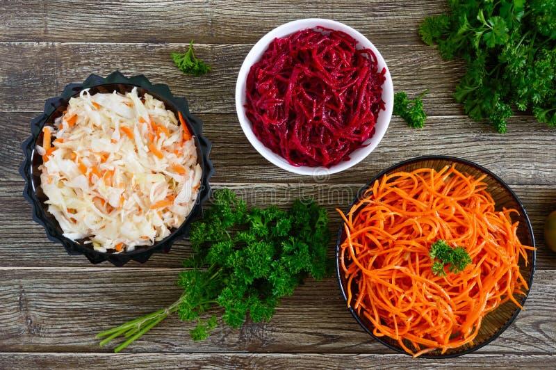 Salades van verse groenten: kool, wortelen, bieten Koreaanse kruidige salades in kommen stock foto