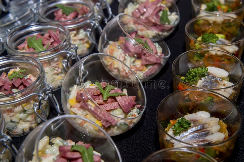 Salads with meat and herring in a glass jar stock photos
