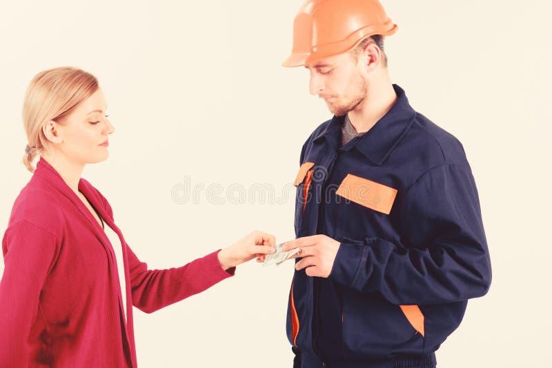 Salaire de cliente de femme à l'homme dans le casque, argent dans des mains image libre de droits