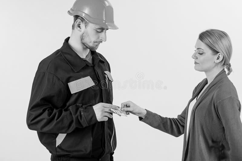 Salaire de cliente de femme à l'homme dans le casque, argent dans des mains images libres de droits