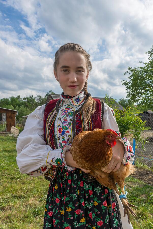 Free Salaj, Transylvania, Romania-May 14, 2020: Beautiful Young Girl In Traditional Romanian Folk Costume Holding A Chicken At A Stock Photography - 217203092