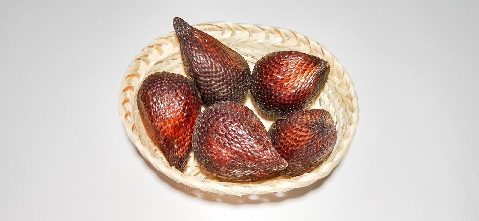 Salak snake fruit on rattan basket. Salak snake fruit is from Indonesian country good for healthy and antioxidant in rattan basket Isolated on white background stock image