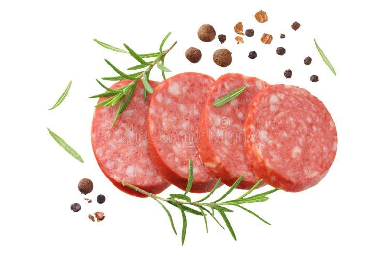 salame affettato della salsiccia con i rosmarini ed i granelli di pepe isolati su fondo bianco Vista superiore fotografie stock